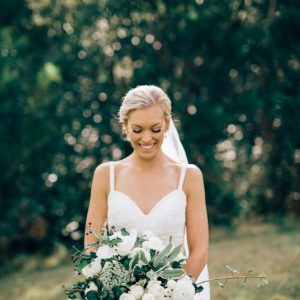 Smiling bride posing with bridal bouquet